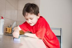 7 year old boy cleans cabinets in the kitchen Royalty Free Stock Images
