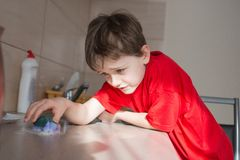 7 year old boy cleans cabinets in the kitchen Stock Images