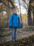 A 7-year-old boy closed his eyes from the sun in an autumn park royalty free stock image