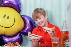 A 10-year-old boy eating a sweet berry pie.On a blue - blue background, close-up. Boy, young, child, desserts, candy, cookies, hap