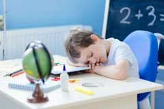 7 year old boy fell asleep while doing homework Royalty Free Stock Photos