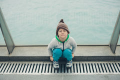 5 year-old boy in a funny hat is sitting and resting on the step Royalty Free Stock Images