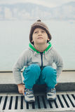 5 year-old boy in a funny hat is sitting and resting on the step Royalty Free Stock Image