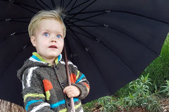 3 year old boy hiding under an umbrella from the rain stock image