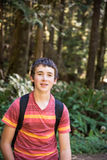 13 year old boy hiking. Thirteen year old boy with backpack, forest behind Stock Image