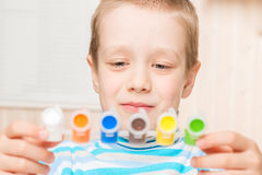 6-year-old boy holding watercolor set. 6-year-old boy holding a watercolor set Royalty Free Stock Image