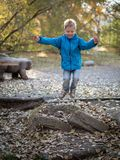 А boy in blue clothes jumps in the park royalty free stock photography