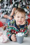 A 5 year old boy lies next to a beautiful Christmas tree holding a large cup of coffee with marshmallows. Five year old boy with short hair,dressed in a bright Stock Images