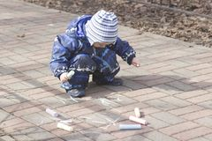 A 2 -year-old boy painting with chalk outdoors. Photo of a two years old boy, wearing dark white-blue-black coveralls and a hat, painting with colour chalk Stock Photo