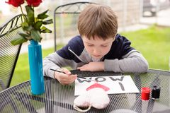 7 year old boy paints greeting card for Mom. Little 7 year old boy paints greeting card for Mom on Mother's Day with the inscription I love you mom. Outdoors Stock Photos