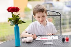7 year old boy paints greeting card for Mom. Little 7 year old boy paints greeting card for Mom on Mother's Day with the inscription I love you mom. Outdoors Stock Images