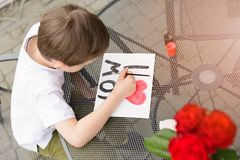 7 year old boy paints greeting card for Mom. Little 7 year old boy paints greeting card for Mom on Mother's Day with the inscription I love you mom. Outdoors Stock Photo