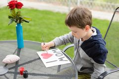 7 year old boy paints greeting card for Mom. Little 7 year old boy paints greeting card for Mom on Mother's Day with the inscription I love you mom. Outdoors Stock Image