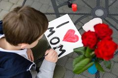 7 year old boy paints greeting card for Mom. Little 7 year old boy paints greeting card for Mom on Mother's Day with the inscription I love you mom. Outdoors Royalty Free Stock Photo