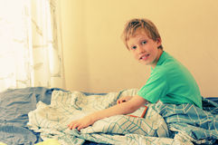 7 year old boy playing with a laptop. 7 year old boy lies in bed and plays with a laptop Stock Photo