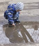 A 2 -year-old boy playing with  in a puddle. Photo of a two years old boy, wearing waterproof  childrens clothing, playing in a puddle in spring. Concept of Royalty Free Stock Photos