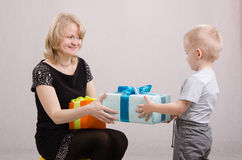 Year-old boy presents a gift to mum. Five children congratulates mother and gives gifts royalty free stock image