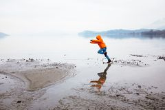 12-year-old boy runs along the beach in winter. Dressed in orange jacket Stock Photo