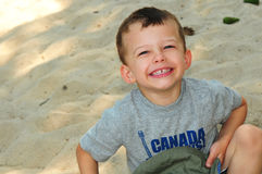 3 year old boy in the sand laughing Royalty Free Stock Image