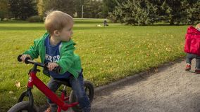 A 5-year-old boy sits on a bicycle and looks back at the departing girl. stock image