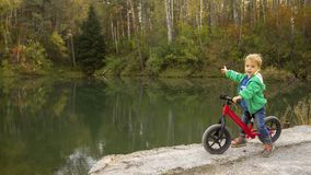 A 5-year-old boy sits on a bicycle by the pond and points to the distance. stock photography