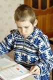 The 10-year-old boy sits with the textbook, doing homework. Royalty Free Stock Images