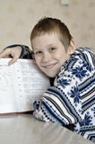 The 10-year-old boy sits with the textbook, doing homework. Royalty Free Stock Image