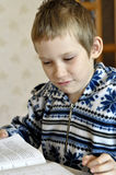 The 10-year-old boy sits with the textbook, doing homework. Royalty Free Stock Photos
