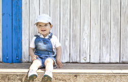 2 year-old boy sitting portrait at wooden beach hut Royalty Free Stock Photography