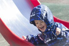 A 2-year-old boy smiling with success. Photo of a a 2-year-old boy, wearing coveralls,  just gone down the slide and expressing happiness of his success Royalty Free Stock Image