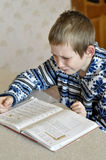 The 10-year-old boy with tears in the eyes sits before the textb. Ook, doing homework Royalty Free Stock Photo