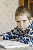 The 10-year-old boy with tears in the eyes sits before the textb. Ook, doing homework Royalty Free Stock Photography