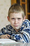 The 10-year-old boy with tears in the eyes sits before the textb. Ook, doing homework Stock Photography