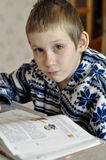 The 10-year-old boy with tears in the eyes sits before the textb. Ook, doing homework Royalty Free Stock Images