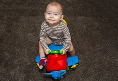 1 year old boy on toy airplane on brown carpet. Stock Image