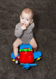 1 year old boy on toy airplane on brown carpet. Finger in mouth. Stock Photo