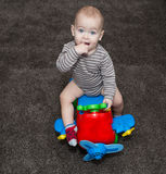 1 year old boy on toy airplane on brown carpet. Finger in mouth. Stock Photos