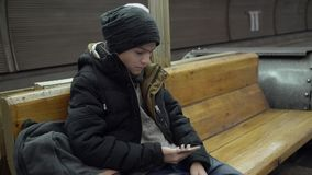 A 15 year old boy in winter clothes is sitting on a bench in the subway. A teenager in winter clothes sits on a bench in the metro and read the sms on the stock footage