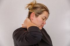 A 38-year-old Caucasian woman with overweight and hormonal disruption demonstrates pain symptoms. On a light isolated background. Concept for medicine and royalty free stock image