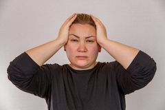 A 38-year-old Caucasian woman with overweight and hormonal disruption demonstrates pain symptoms. On a light isolated background. Concept for medicine and royalty free stock images