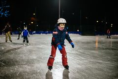 10 year old childl skates on the ice in the evening on an illumi Royalty Free Stock Photo