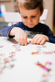 2 year old child solving jigsaw puzzle Royalty Free Stock Images