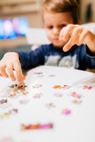 2 year old child solving jigsaw puzzle Royalty Free Stock Photos
