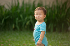 1 year old Chinese Asian boy wearing rompers in a garden Stock Photos