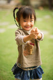 5 year old Chinese Asian girl in a garden making faces Royalty Free Stock Images