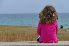 3-4 year old girl looking at the sea stock photo