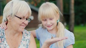 Grandmother with her granddaughter looking at a small snail in her hand. Concept - nature and life around, active