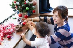 1-year-old girl and mother decorating Christmas tree by window in living room Royalty Free Stock Photos