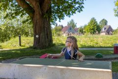 A schoolgirl plays table tennis. She is focused on hitting the b. A 7 year old girl plays table tennis on an outside ping-pong table. She is focused on hitting Stock Image