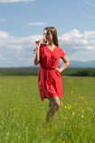 20 year-old girl in red dress sniffing a yellow flower Royalty Free Stock Photography